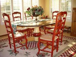 painted red vintage wooden chairs and oval kitchen table in a yellow dining room with an area rug