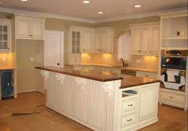 white wooden kitchen island and kitchen cabinet with brown glossy countertop on laminate