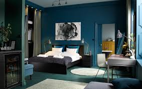 A medium sized bedroom furnished with a black-brown bed for two combined  with chest