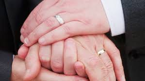 gay marriage wedding rings. two men holding hands with wedding rings gay marriage w