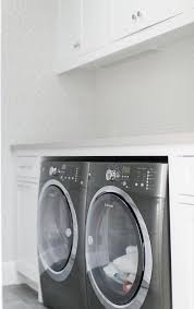 white laundry room cabinets with light gray quartz countertops