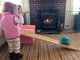child playing in front of wood stove with fire safety gate wood stove vs