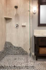 This shower brings elements of nature with a shower pan tiled with pebble  mosaic. #