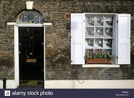 decorations and viola flowers in window box outside a house with black door fanlight