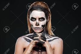 stock photo woman with frightening skeleton makeup over black background