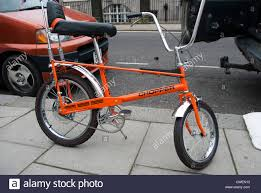 orange raleigh chopper bicycle parked on stone flagged pavement