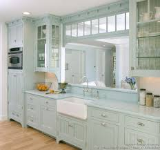 A Pale Blue Victorian Kitchen With Matching Blue Countertops, A White Apron  Sink, Glass