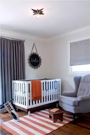 gray and orange nursery with orange striped rug