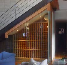 wine cellar under the stairs encased in frameless glass vint wine racking works well in