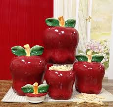 apple red ceramic decorative kitchen canisters sets over white table cloth and marble countertop facing small window in red painted kitchen wall