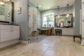 stone floor slate wall blue wall white cabinet mirror freestanding tub pendant lights vessel sink glass