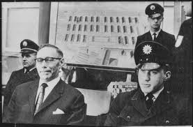 holocaust what is happening now main defendant wilhelm boger on the photo left awaits the beginning of the frankfurt auschwitz trial in 1964 in the background a map of the