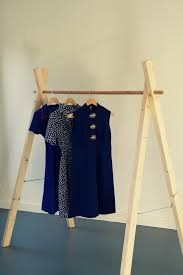 View in gallery. A freestanding clothing rack made of wood ...