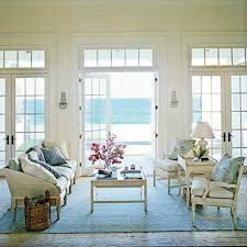 coastal cottage chic living room with white washed wood sofa and chairs pale blue fabrics is and is ancd with a great blue raffia pattern area rug