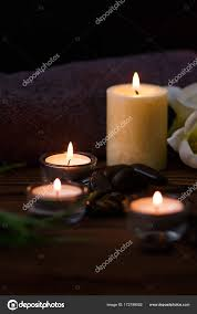 a candle in a glass vase decoration and various interesting elements on a dark wooden background candles burning set for spa and massage stones for