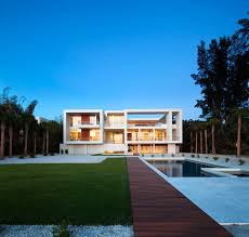 a dark wood walkway leads through the backyard of this home dividing the grassy space and the pool area