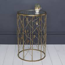 round gold metal side table with a glass top and vine and leaf design base