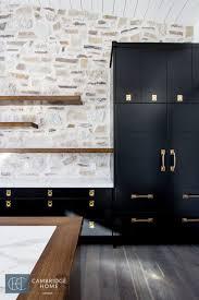 semi transpa black kitchen cabinets and rock wall kitchen back splash in an industrial farmhouse kitchen