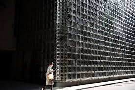 a woman walks out of the maison hermes building designed by italian architect renzo piano