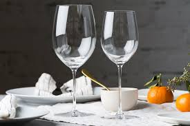 two wine glasses on a table decorated with plants plates and pieces of citrus