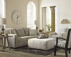 light toned living room stands over grey hardwood flooring with neutral grey sofa next to