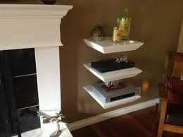 triple white wooden shelves with square shelves placed on the brown wall beside fireplace terrific