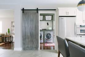 a gray barn door on rails opens to a cote laundry room filled with a gray enclosed washer and dryer topped with black laminate countertop under overhead
