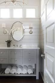 an elegant oval mirror gives the linear bathroom a hint of curves satin nickel