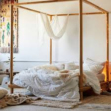 fl comforter adorning a four poster bed in a bohemian bedroom