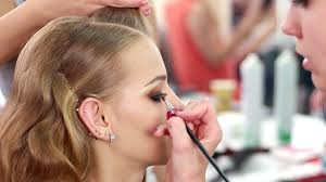 makeup eyeliner eye shadow makeup artist stylist working with a client in the beauty salon eye shadow brush for shadows design of eyebrows in a