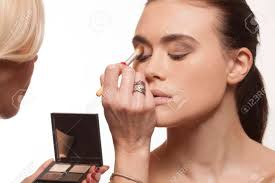 beautician applying eye makeup to the eyelids of an attractive young model before a photo shoot