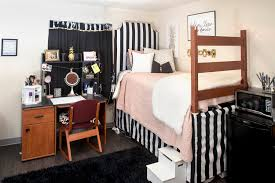dorm room with bed desk and various decor