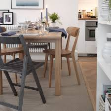 image of a wooden extendable table with chairs in a kitchen diner setting