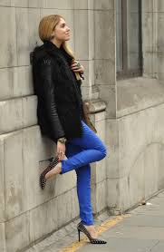 go for a black fur vest and layer it over black leather jacket complete this look by adding bright blue skinny pants and studded sti black pumps