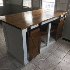 custom shiplap kitchen island with sliding barn doors and food prep ready counter top painted white with provincial stain top and doors