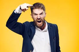 an angry man with a beard stands in front of a bright orange background and shouts