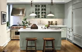 Other kitchen ideas such as brass or rubbed nickel door pulls and wooden  chairs with blue cushions keep everything anchored.