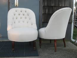 tufted slipper chair in off white fabric on rosewood feet with brass wheels on front legs