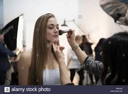 female makeup artist apply makeup to model preparing model for photo shoot in studio