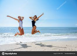 two funny s beautiful bos swimwear jumping tropical beach funny stock photo