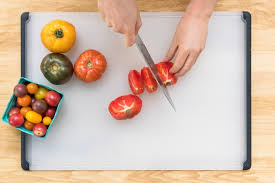 cutting board with food. An Overhead Shot Of A Person Slicing Tomatoes On Plastic OXO Cutting Board . With Food
