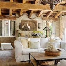 rustic tuscan living room with wooden ceiling and white sofa and stone flooring and traditional lighting