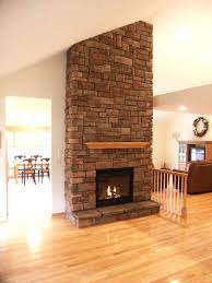 light brown laminate hardwood flooring with white walls and ceilings stack stone black frame glass fireplace