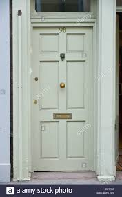 gray painted wooden paneled front door no 98 with brass letterbox and fanlight of house in uk