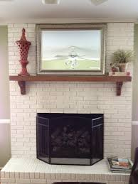 painted brick fireplace with white brick stone fireplace having transpa cover on beige wall