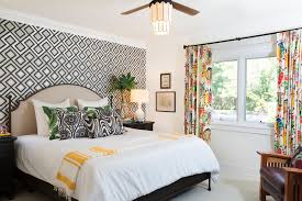 Accent wall with geometric wallpaper and colorful drapery in playful  bedroom.
