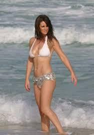 Com uma silhueta esbelta e cabelo preto sem sutiã (tamanho ) em biquini na praia