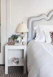 chic bedroom features a light blue headboard with silver nailhead trim on bed dressed in white scalloped bedding next to a west elm parsons end table atop a