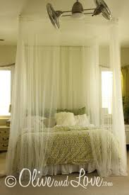 DIY Ceiling mounted bed canopy consisting of eyebolts, turn buckles and  wire thread through sheer curtains. So romantic