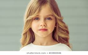 portrait of pretty little blonde with beautiful big eyes looking at camera